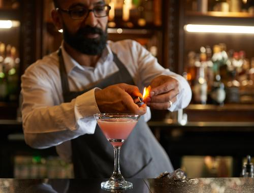 Bartender at the bar lighting a cocktail on fire